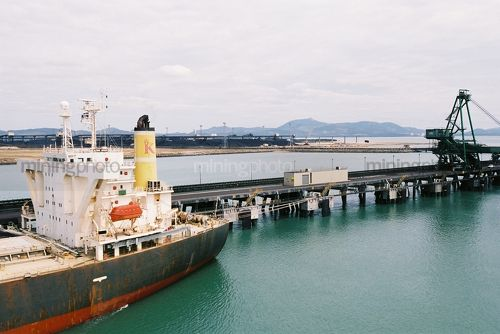 Ship at terminal with coal stockpiles in background - Mining Photo Stock Library