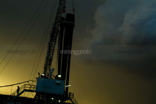 Silhouetted worker walking down stairs of drill rig during afternoon thunderstorm  - Mining Photo Stock Library