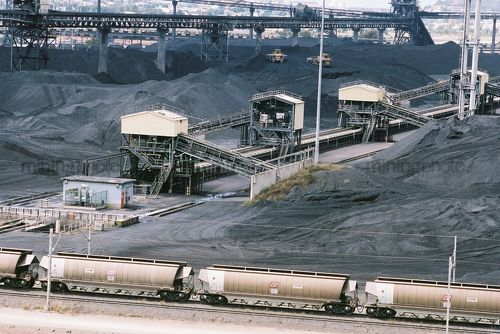 Heavy rail carts emptying coal at wharf terminal with stockpiles coal in background - Mining Photo Stock Library