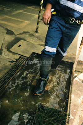 Male underground worker walking through water trough to clean his boots after shift.  shot without seeing head. - Mining Photo Stock Library