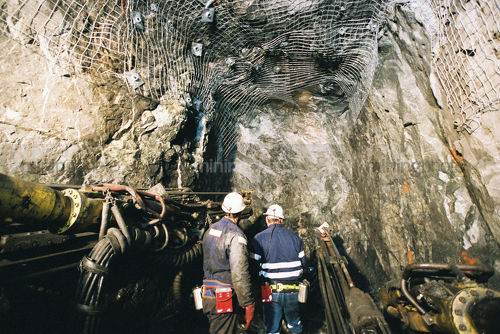2 underground mine workers inspect machinery and drilling area. - Mining Photo Stock Library