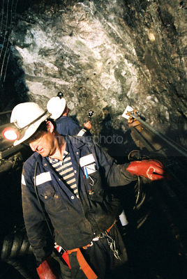 Underground worker returning to machinery with other miner inspecting roof in background. - Mining Photo Stock Library