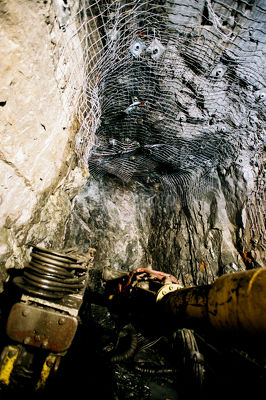 Underground machinery jumbo arm drilling holes for mesh anchors - Mining Photo Stock Library