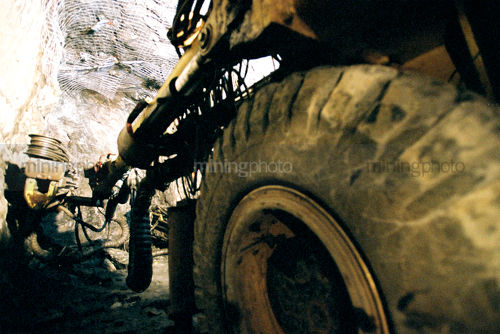 Underground jumbo machinery drilling holes for mesh anchors.  shot looking along from back wheel. - Mining Photo Stock Library