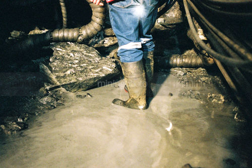 Underground mine worker in gumboots organising water pump system.  shot from behind and from the waist down. - Mining Photo Stock Library