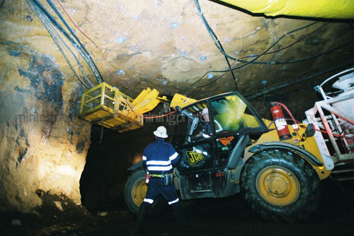 2 mine workers underground discussing how to place mesh anchors to hold roof.  machine cherry picker in use. - Mining Photo Stock Library