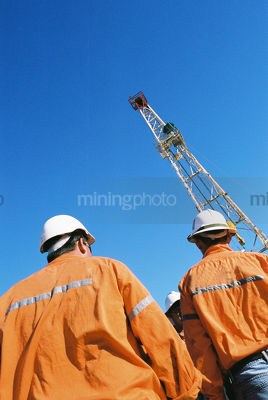 Drill rig workers with derrick behind - Mining Photo Stock Library