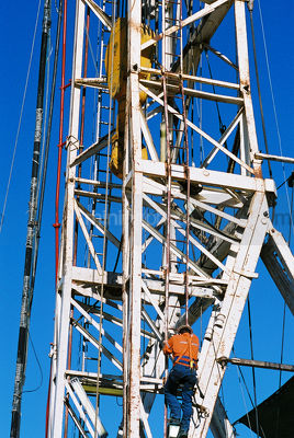 Drill rig worker climbing up the outside of the derrick - Mining Photo Stock Library
