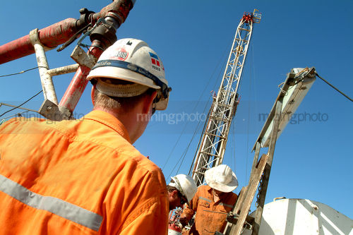 Drill rig workers with derrick behind.  shot from behind. - Mining Photo Stock Library