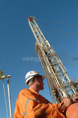 Oil and gas worker on mine site with drill rig derrick behind.  shot from  the side. - Mining Photo Stock Library