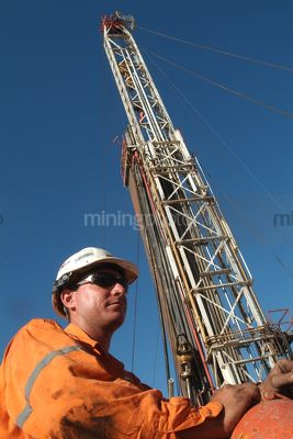Oil and gas worker on mine site with drill rig derrick behind.   - Mining Photo Stock Library