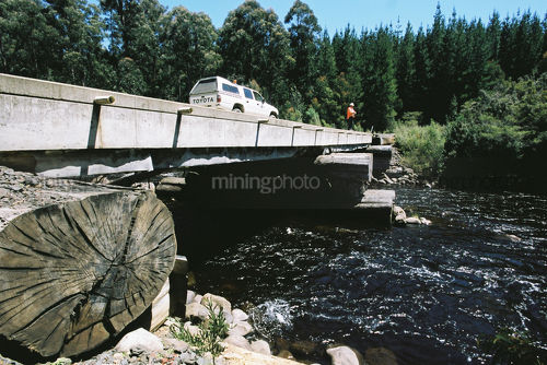 Light vehicle on log bridge with clean fresh water flowing under it.  forestry worker standing on edge of bridge. shot from edge of bridge. - Mining Photo Stock Library