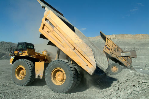 Haul trucks emptying coal overburden onto stockpile - Mining Photo Stock Library