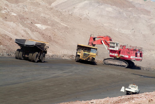 Large excavator loading a haul truck while an empty truck is nearby.  light vehicle in foreground for scale.  opencut mine site. - Mining Photo Stock Library