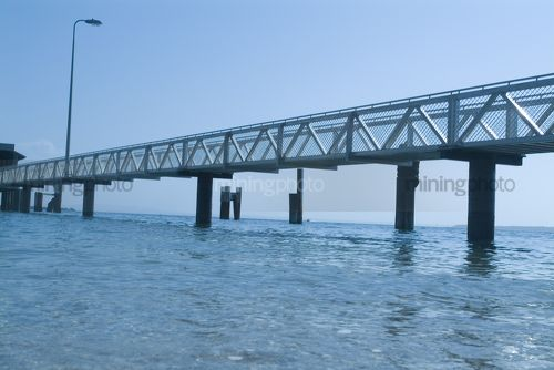 Pedestrian jetty out to passenger ferry terminal over ocean.  shot from water level. - Mining Photo Stock Library