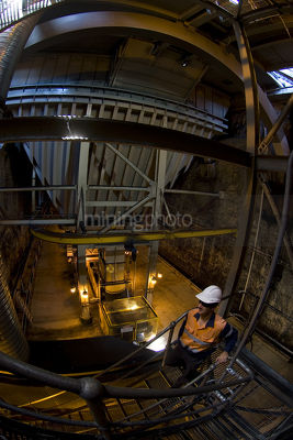 Mine worker in PPE descending stairs underground to rail carriage hopper and coal conveyor.  - Mining Photo Stock Library