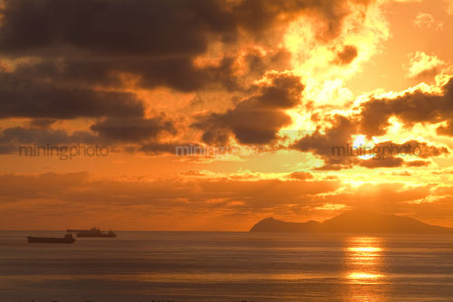 Ships anchored offshore at port terminal waiting to be loaded.  brilliant morning sunrise. - Mining Photo Stock Library