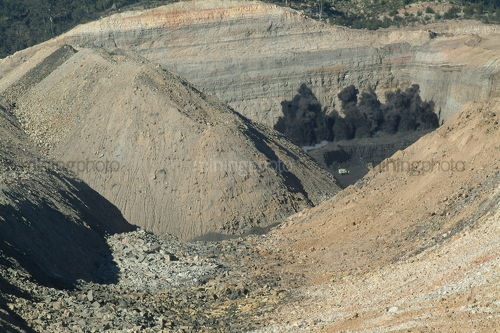 Spetacular opencut coal blast on mine site floor with high walls around - Mining Photo Stock Library