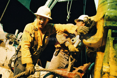 Great teamwork photo of two oil rig workers wrestle a huge cable onto the hook of the derrick. shot at night. - Mining Photo Stock Library