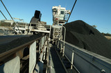 Mining Photo Stock Library - moving conveyor of coal track loader  with stockpiles in background. ( Weight: 4  New Image: NO)