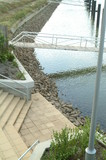Mining Photo Stock Library - steps leading down to water in canal property subdivision.  jettys and pedestrian bridges to pontoons in background. ( Weight: 3  New Image: NO)