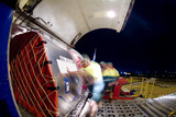 Mining Photo Stock Library - workers in PPE rolling large cargo boxes into hold of plane. shot at night. ( Weight: 1  New Image: NO)