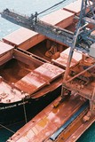 Mining Photo Stock Library - looking down into ships holds as bauxite is being unloaded by shiploader crane.  aerial closeup image ( Weight: 1  New Image: NO)