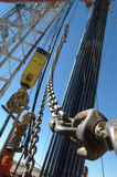 Mining Photo Stock Library - chain and cables on oil and gas rig with derrick behind. ( Weight: 2  New Image: NO)