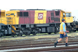 Mining Photo Stock Library - rail worker crossing tracks with heavy train engine in background. ( Weight: 1  New Image: NO)