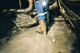Mining Photo Stock Library - underground mine worker in gumboots organising water pump system.  shot from behind and from the waist down. ( Weight: 1  New Image: NO)