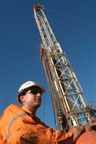 Mining Photo Stock Library - oil and gas worker on mine site with drill rig derrick behind.   ( Weight: 1  New Image: NO)