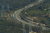 Mining Photo Stock Library - trucks on highway through forest with electricity supply power lines adjacent.  aerial shot. ( Weight: 2  New Image: NO)