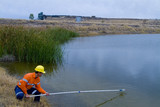 Mining Photo Stock Library - mine environment worker taking water samples from dam at open  cut mine.  haul truck on road in background. ( Weight: 1  New Image: NO)