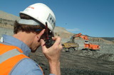 Mining Photo Stock Library - mine site supervisor listening to radio with excavator loading haul truck in background. ( Weight: 3  New Image: NO)