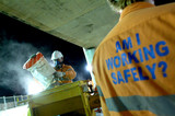 Mining Photo Stock Library - construction worker wearing a safety mask works with concrete bags at night. another worker with signage on his shirt promoting safe work practices is in foreground. ( Weight: 4  New Image: NO)