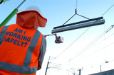 Mining Photo Stock Library - site worker watching large concrete girder being craned into position with overhead rail electricity wires. ( Weight: 3  New Image: NO)