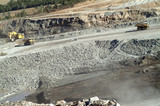 Mining Photo Stock Library - aerial shot of open cut coal mine with 2 truck rotation, excavator loading and small light vehicle in there for scale.  blasting setup hole sin background. ( Weight: 4  New Image: NO)