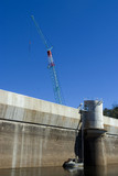 Mining Photo Stock Library - vertical shot close up of dam wall and construction crane with maintenance boat in the water. deep blue sky. ( Weight: 4  New Image: NO)