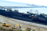 Mining Photo Stock Library - coal terminal conveyor running out to ship being loaded at the wharf.  stockpiled coal and reclaimers working in middle ground. Earthworks and heavy machinery in foreground. ( Weight: 2  New Image: NO)