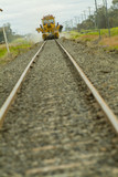 Mining Photo Stock Library - looking along rail track at ground level to track maintenance in distance.  foreground track out of focus. ( Weight: 4  New Image: NO)