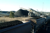 Mining Photo Stock Library - heavy rail carriages loaded with coal in foreground with stacker stockpiling coal in background. ( Weight: 2  New Image: NO)
