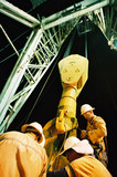 Mining Photo Stock Library - workers in PPE inspecting the derrick on a drill rig.  shot at night and looking up the derrick for full height.  vertical shot ( Weight: 1  New Image: NO)