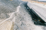 Mining Photo Stock Library - three truck rotation with digger on coal seam floor with steep high walls.  water cart in background and long haul road behind. midden overburden stockpiles on side.  image shows scale of huge size and depth of mine.   ( Weight: 1  New Image: NO)
