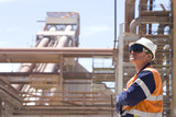Mining Photo Stock Library - process engineer onsite in full ppe wearing ear plugs gazing upwards with arms folded.  pipeline and plant in background.  worker is on right hand side of frame.  great generic shot. ( Weight: 1  New Image: NO)