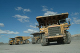Mining Photo Stock Library - large haul truck leaving the go line at the shift change.  shot from ground level to show size of truck. trucks in the background lined up. ( Weight: 2  New Image: NO)