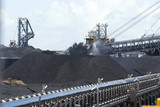 Mining Photo Stock Library - coal reclaimer and ship loader working on coal stockpiles at terminal. moving coal conveyor in foreground.  water sprinklers for dust suppresion working as well.  great production image. ( Weight: 1  New Image: NO)