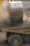 Mining Photo Stock Library - close up of digger bucket loading haul truck with overburden in open cut mine.  lots of dust. ( Weight: 3  New Image: NO)