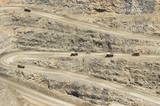 Mining Photo Stock Library - many haul trucks loaded and empty weaving their way up steep haul road on way out of open cut gold mine. ( Weight: 1  New Image: NO)