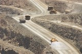 Mining Photo Stock Library - water cart spraying water oin haul road with loaded and empty haul trucks n background. ( Weight: 1  New Image: NO)