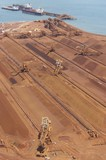 Mining Photo Stock Library - aerial vertical shot of many reclaimers working and loading iron ore onto conveyors.  ship and shipping port terminal in background with ocean. ( Weight: 1  New Image: NO)